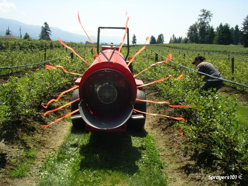 Ribbons tied to each active nozzle position will show where air (and spray) is aimed. Note the slight downward direction of the air on the bottom-left side of the sprayer versus the bottom-right. Don't use flagging tape, as shown here. Not only will it stretch beyond 25 cm, but it often breaks. I once covered an orchard floor with orange flagging-tape confetti; it was funny, but not terribly informative. Use 25 cm lengths of strong ribbon instead. Photo Credit – M. Waring, British Columbia.