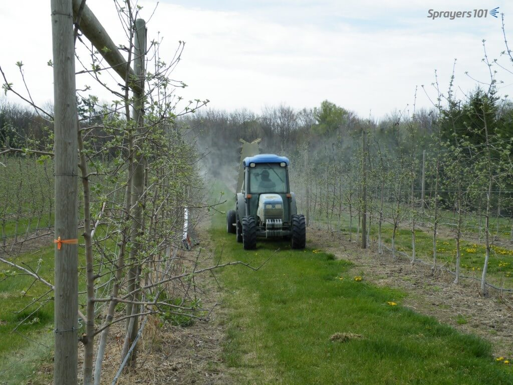 It's early May in Southern Ontario. This high-density orchard is receiving ~355 liters/ha (~38 gal.ac) for spring protectant fungicide applications. A cross wind is coming from the driver's right, gusting up to 10 km/h. The sprayer fan is in low gear, travelling 6.1 km/h (3.8 mph). Experience in this orchard over recent years tells us that we do not need to raise the output over the season because as the trees fill in, the cross wind will be less, and more spray will be available for coverage.